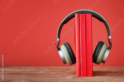 Foto  Books and modern headphones on table. Concept of audiobook