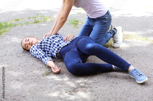 Fotomural  Female passer-by doing CPR on unconscious woman outdoors