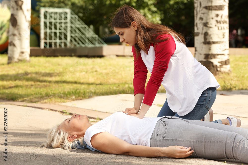 Fototapety, obrazy: Female passer-by doing CPR on unconscious mature woman outdoors