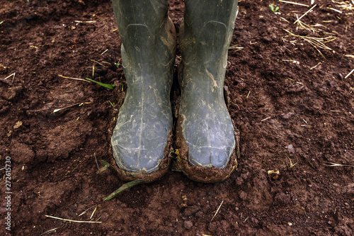 Dirty farmer's rubber boots on muddy country road - 272615730