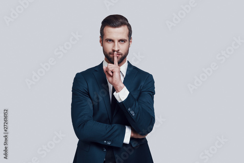 Keep silence! Handsome young man working keeping finger on lips while standing a Fototapet