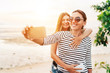 Two caucasian girlfriends hugging and posing for selfie on the sea side using smartphone. Careless vacation time concept image.