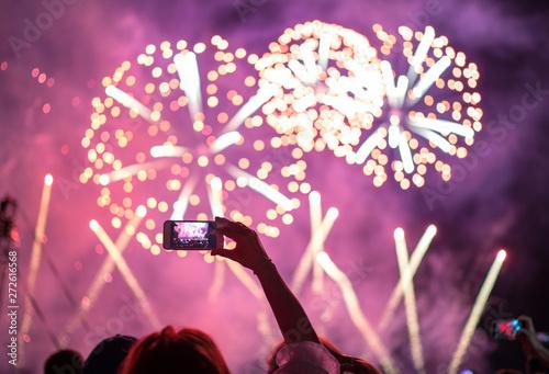 Foto  Raised hand with shooting horizontal night fireworks sky video smartphone