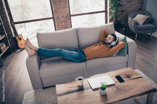Proofile side top above high angle view photo of handsome trendy stylish man close eyes feel quiet lie divan weekend free time vacation orange pullover sweater big apartment