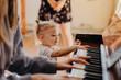 Leinwandbild Motiv Cute little happy child girl playing piano in a light room. Selective focus, noise effect