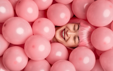 Cheerful ethnic woman in pink wig lying under balloons