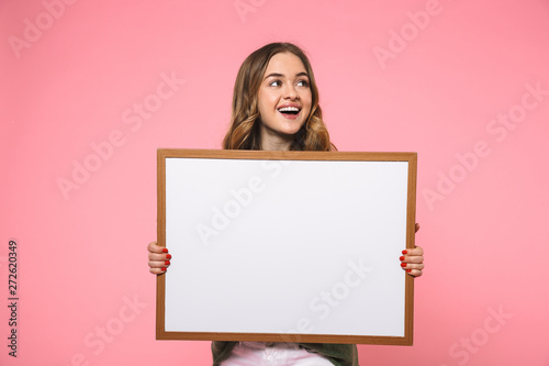 Cheerful blonde woman holding blank board and looking away