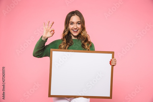 Cuadros en Lienzo  Happy blonde woman holding blank board and showing ok sign