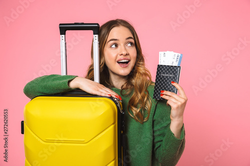 Fotografiet Intrigued blonde woman wearing in green sweater posing with baggage