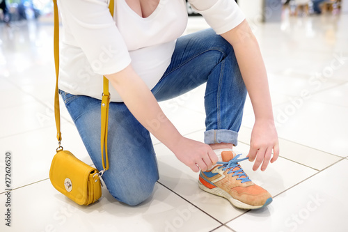 Fotografía  Young pregnant woman lacing up sneakers in hall of shopping mall