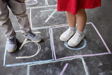 Closeup Of Little Boy's And Girl's Legs And Hopscotch Drawn On Asphalt. Child Playing Hopscotch Game On Playground Outdoors On A Sunny Day.