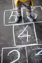 Closeup Of Little Boy's Legs And Hopscotch Drawn On Asphalt. Child Playing Hopscotch Game On Playground Outdoors On A Sunny Day.