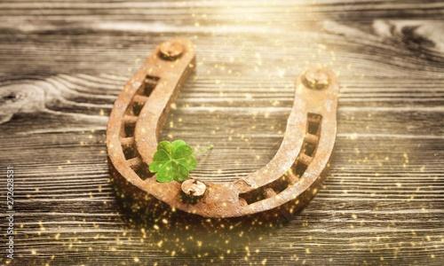 Obraz na plátně Metal horseshoe and cloverleaf on wooden table