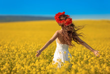 Beautiful Young Woman With Long Healthy Hair Over Yellow Rape Field Landscape Background. Attracive Brunette Girl With Red Poppy Wreath On Hairstyle, Outdoor Portrait. Natural Beauty.