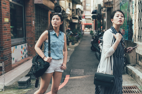 two young asian girl tourists consulting right way in city using smartphone gps in street searching locations Wallpaper Mural