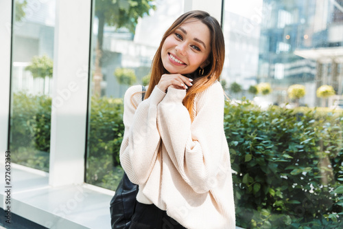 In de dag Eigen foto Photo of beautiful lovely woman smiling at camera with hands together while sitting near window in building indoors