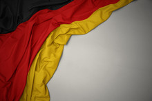 Waving National Flag Of Germany On A Gray Background.