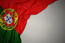 Waving National Flag Of Portugal On A Gray Background.