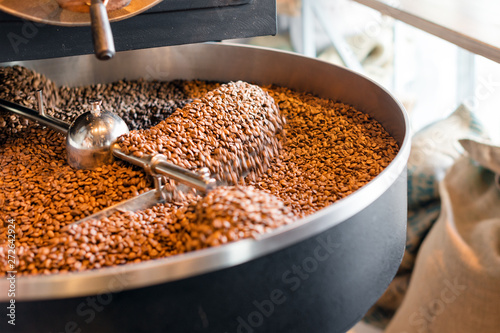 Freshly roasted coffee beans from a large roaster in the cooling cylinder. Motion blur on the beans, selective focus - 272642924