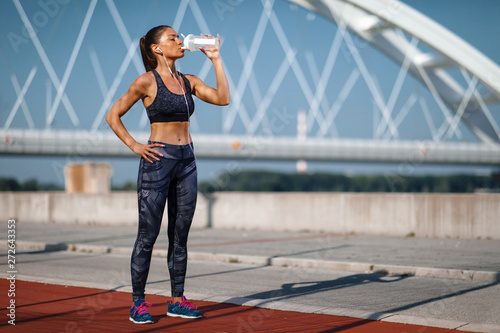 Poster Ecole de Danse Young woman resting after jogging and drink water on a sunny day