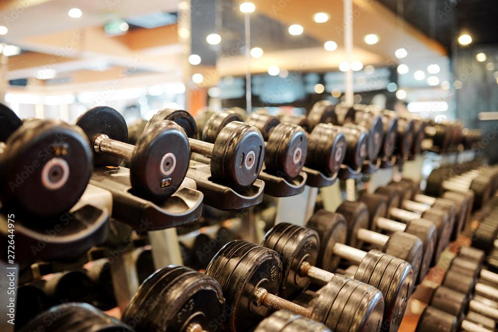 Fototapeta Rows of metal dumbbells on rack for strength training in gym