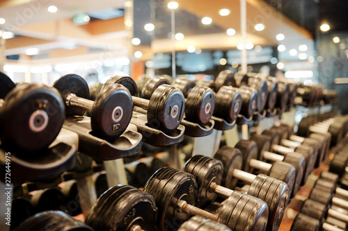 Poster Fitness Rows of metal dumbbells on rack for strength training in gym