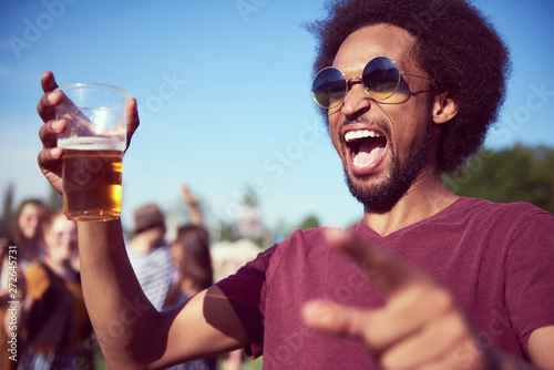 Screaming African man drinking beer at the music festival - 272645731