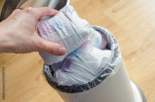 Woman hand put used diaper to the Trash bin full of used diapers Fototapet