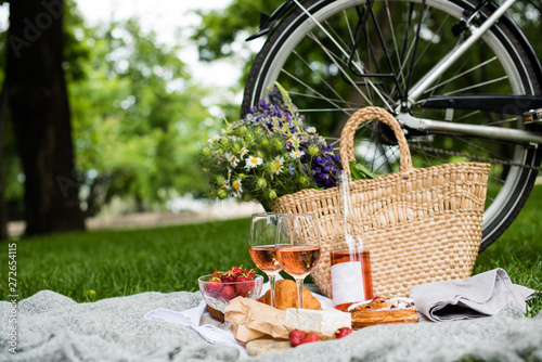 Beautiful summer picnic with strawberries, cheese and rose wine on the lawn in t Fotobehang