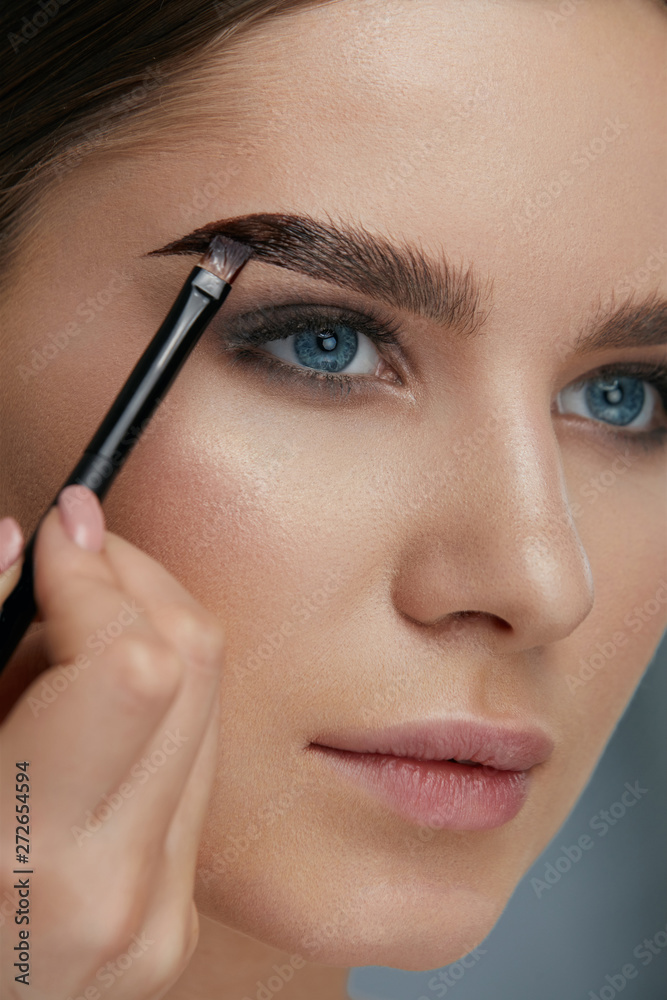 Fototapety, obrazy: Eyebrow coloring. Woman applying brow tint with makeup brush