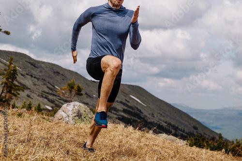 Canvastavla  male runner athlete running uphill trail in summer outdoor