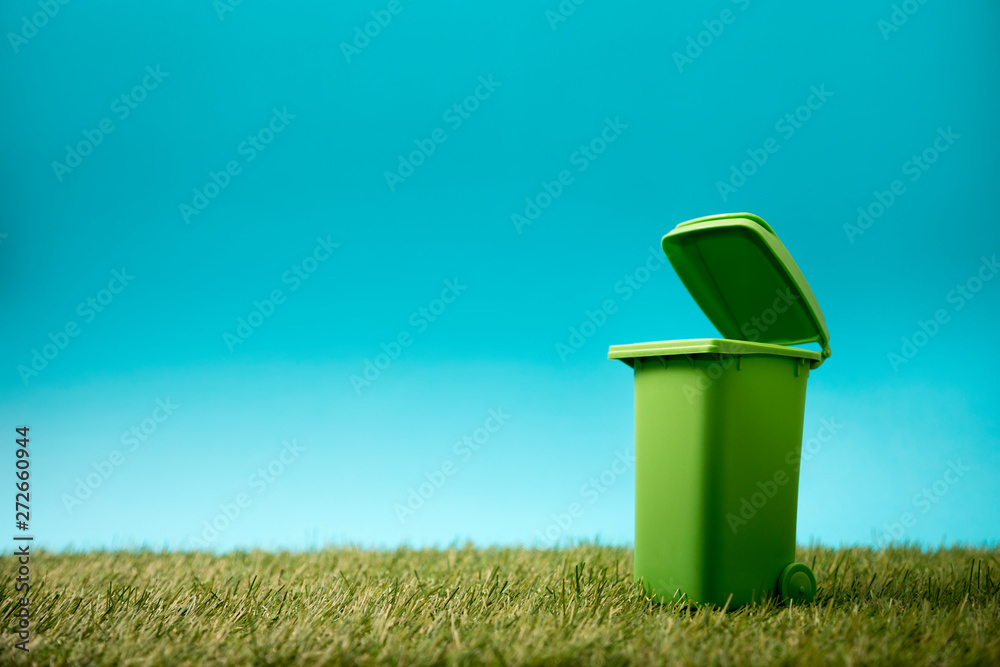 Green recycle bin on green grass and blue sky