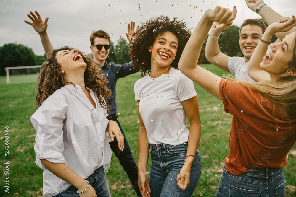 Fototapeta Group of five friends having fun at the park - Millennials dancing in a meadow among confetti thrown in the air - Day of freedom and carefree
