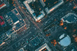 Aerial top view of city asphalt roads with lot of vehicles or car traffic and buildings, modern urban intersections and junctions in midtown