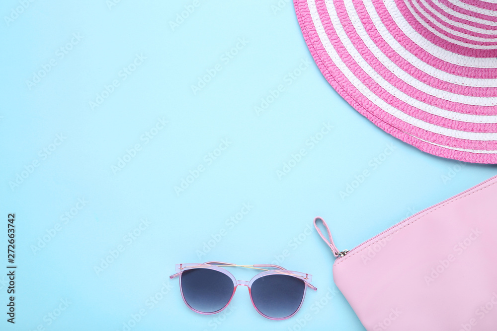 Beach hat with bag and sunglasses on blue background