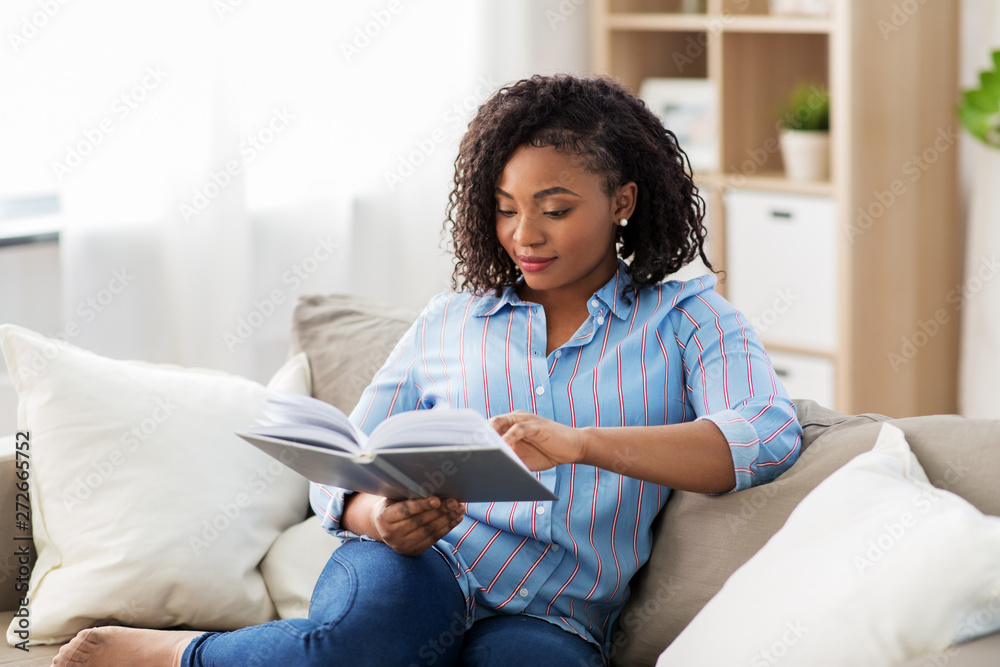 Fototapeta leisure, literature and people concept - african american woman reading book at home
