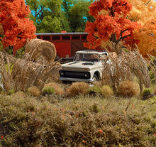 Weathered White Pickup Truck Parked In Front Of Orange Farmland Barn With Autumn Trees