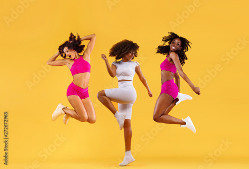 Three strong and happy athletic women, jumping or dancing on yellow background wearing color sportswear. Fitness and sport motivation. - 272672968