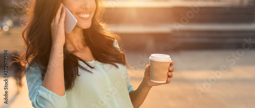 fototapeta na lodówkę Girl enjoying coffee and phone talk, walking in city at sunset