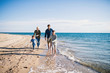 canvas print picture Young family with two small children running outdoors on beach.
