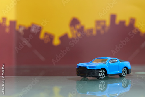 Fotografie, Obraz  blue muscle car toy selective focus on blur city background