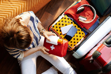 Woman Packing First Aid Kit And SPF In Open Travel Suitcase