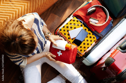 Obraz woman packing first aid kit and SPF in open travel suitcase - fototapety do salonu