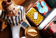 Smiling Woman Using Mobile Travel Agent App On Smartphone