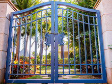 Antique Steel Blue Double Gate With Padlock In Front Of A Tropical Garden