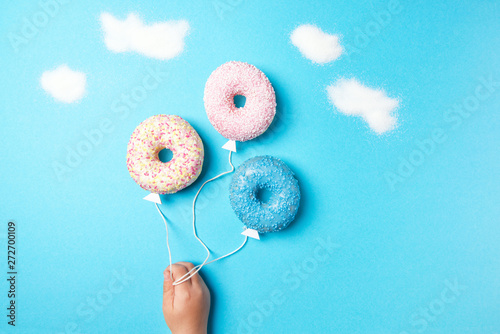 Colorful donuts on blue background, creative food minimalism, donuts in a shape Wallpaper Mural