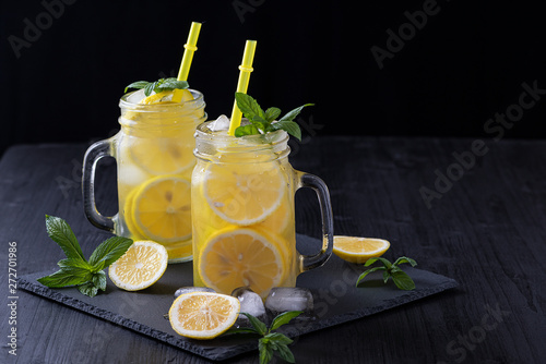 Fototapeta Lemonade in a jar with ice and mint on a black wooden table.