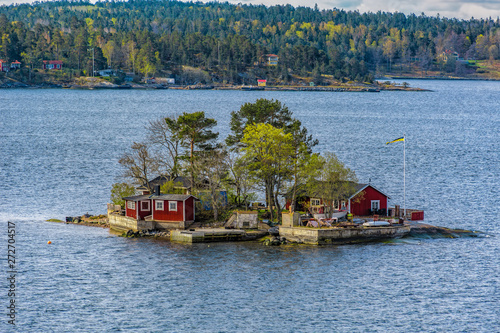 Photo Picturesque summer houses painted in traditional falun red on dwellings island in Stockholms Skärgården (Stockholm Archipelago) in Baltic sea at spring sunny morning