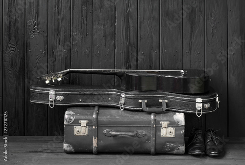 Photo  black guitar and a suitcase against a black wooden background