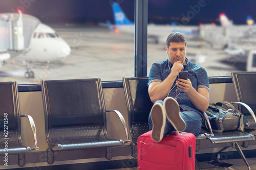 Fotografía  Middle age man tourist using smart phone in airport terminal looking at flight s